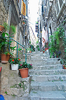 View from the Prijeko street up a narrow side street with steep stairs. Narrow cobble stone street. Many pots and plants with flowers and hand rails. Dubrovnik, old city. Dalmatian Coast, Croatia, Europe.