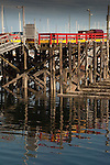 Old wooden pier reflected in the water on the Campbell river. Vancouver Island, British Columbia, Canada.