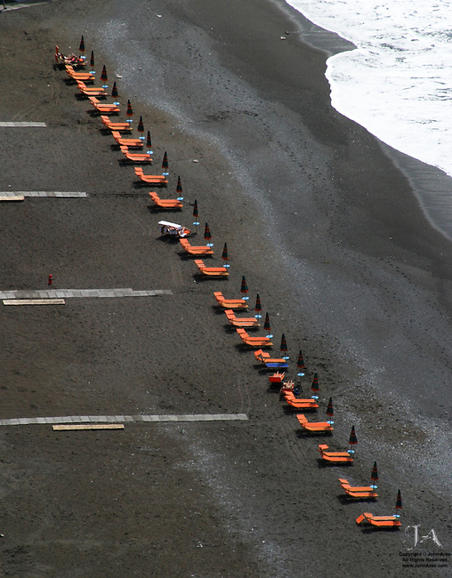 Beach chairs on the black sand of Positano's famous beach.