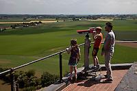 turisti osservanocon un cannocchiale il campo di battaglia di Waterloo dall'alto della collina del Leone