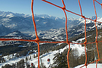 Switzerland. Valais. Crans Montana. View on the Rhone valley. Winter ski resort. View through the safety net on the CMA ( Crans Montana Aminona) red cable cars which are carrying people to the top of the mountain on a sunny day with blue sky. View on the Rhone valley. © 2005 Didier Ruef