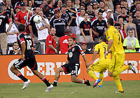 WASHINGTON, DC - AUGUST 4, 2012:  Chris Kolb (22) of DC United passes to Nick DeLeon (18) as Dilly Duka (11) of the Columbus Crew moves in during an MLS match at RFK Stadium in Washington DC on August 4. United won 1-0.
