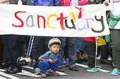 London, UK. 17 September 2016. A little Asian boy crouches under a Sanctuary banner. Thousands of people take to the streets in a Refugees Welcome march in Central London ahead of a meeting of world leaders discussing the refugee crisis in New York.