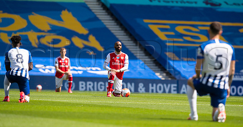 20th June 2020, American Express Stadium, Brighton, Sussex, England; Premier League football, Brighton versus Arsenal ;  Arsenals Alexandre Lacazette takes a knee with teammates in support of the Black Lives Matter campaign prior to the Premier League match