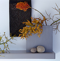 A narrow shelf houses a contemporary vase filled with exotic plants from the garden