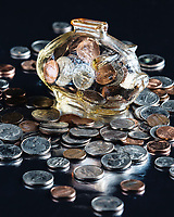 Piggy bank, glass, surroundied by U.S. coins on black background.