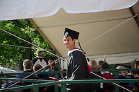 Young man walking with his new diploma, Clark University, Worcester MA, 2012