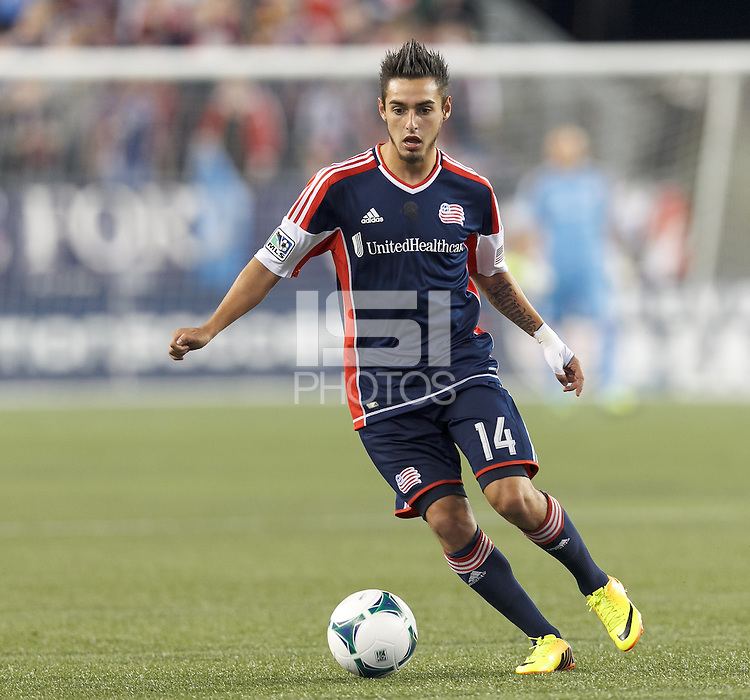 New England Revolution midfielder Diego Fagundez (14) brings the ball forward.  In a Major League Soccer (MLS) match, the New England Revolution (blue) defeated Columbus Crew (white), 3-2, at Gillette Stadium on October 19, 2013.
