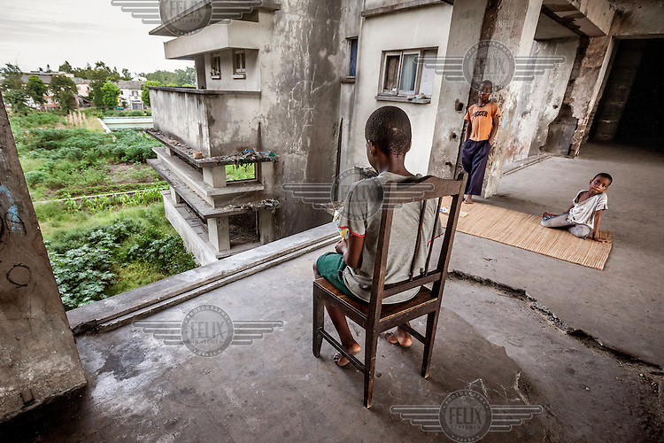 Eddi Ramires (9) sits on the chair in a corridor in the former Grand Hotel. The building is not safe, especially for children, and it is not uncommon for them to fall from the building's open floors, resulting in injures or death.