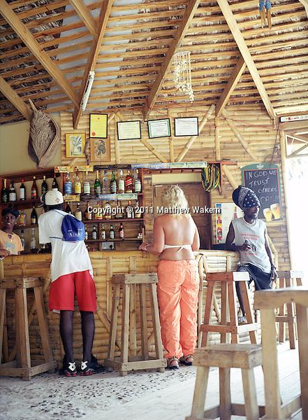 CAS EN BAS, ST.LUCIA : Tourists and locals hang out at Marjorie's Beach Bar on Cas En Bas beach. Cas En Bas, St. Lucia, W.I.