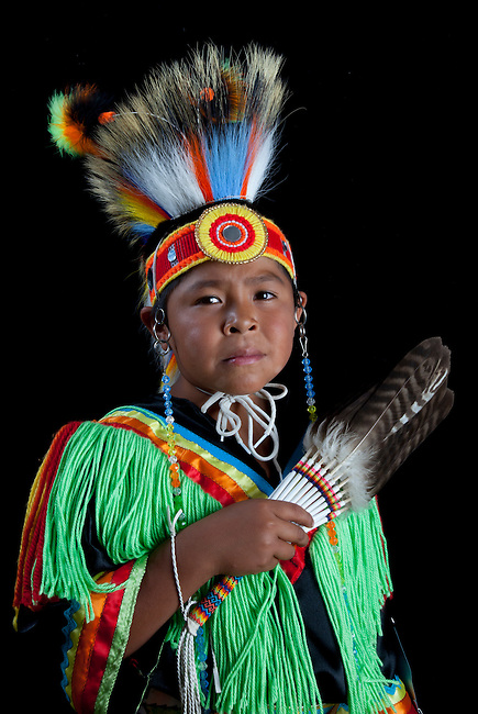 10 years old Thomas Tom (Temoke-Shoshone) dressed in colorful grass dancer outfit and roach headdress with black background