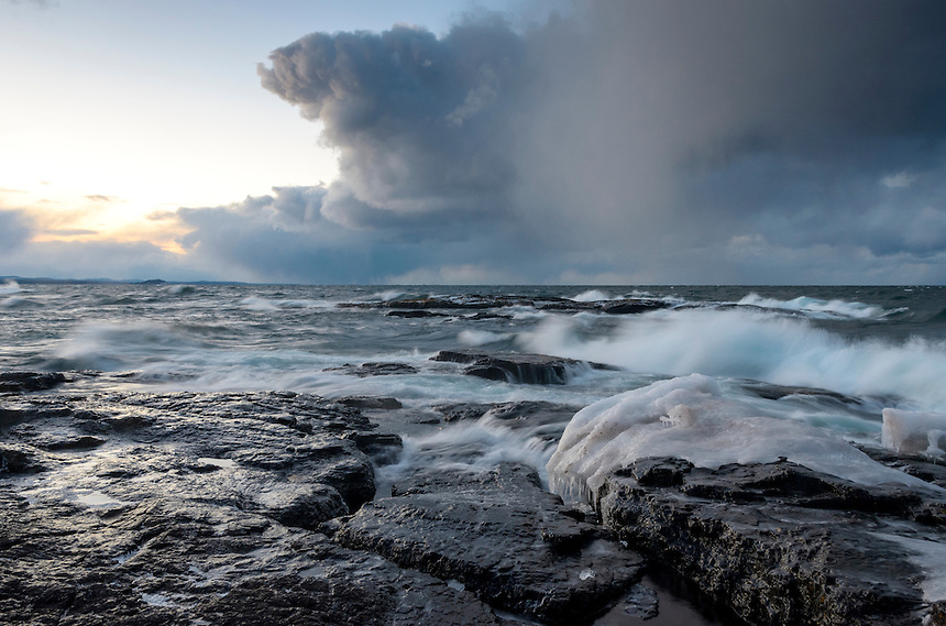 Storm clouds moving over Lake Superior and waves crashing ashore at the rugged Black Rocks of Presque Isle Park. Marquette, MI