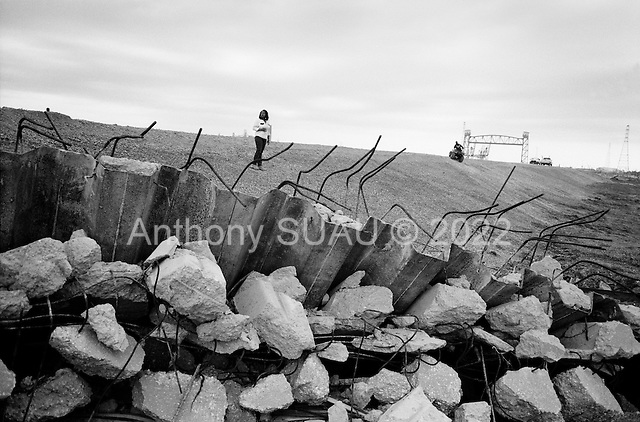 New Orleans, Louisianna.USA.December 1, 2005 ..Hurricane Katrina damage and recovery. Residents of the Lower Ninth Ward return to their homes for the first time. A few residents climb the gravel hill of the new levee above their destroyed homes.