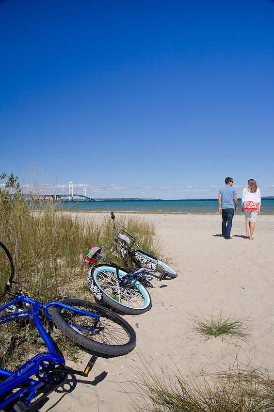 A couple park their bikes and explore a beach with a view of the Mackinac Bridge in Mackinaw City, Michigan.