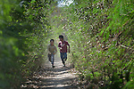 Juan Lovenzo (left) and Nelson Romero, both Wichi indigenous boys, run through the forest near their home in Lote 75, an indigenous neighborhood of Embarcacion, Argentina. The Wichi in this area, largely traditional hunters and gatherers, have struggled for decades to recover land that has been systematically stolen from them by cattleraisers and large agricultural plantations.