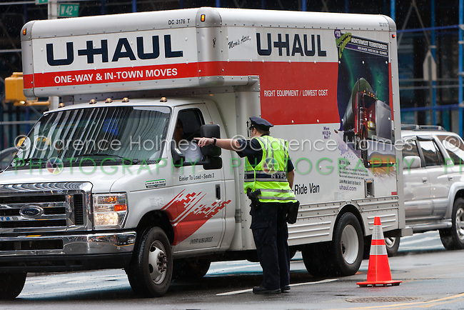 A NYPD police officer directs a truck through a security checkpoint on 44th Street between 7th and 8th Avenues.