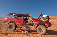 """Derek Krantz, of Moab, Utah, looks for the cause of a failing front drive system on his Jeep as his children Jeremy Christensen, 6, center, Mikala Christensen, 4, in pink, and Autumn Krantz, 3, play in and under the truck. Krantz was attempting to climb the """"Dump Bump,"""" a challenging sandstone step above Moab, Utah, Friday, April 15, 2005, when his truck failed. After a uranium mining bust in the early 1980s, Moab has reinvented itself as a recreation mecca, attracting conflicting groups of mountain bikers, off-road drivers, climbers, hikers and rafters. (Kevin Moloney for the New York Times)"""