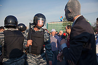 Moscow, Russia, 06/05/2012.. A riot policeman faces off against a masked protestor at opposition demonstration against Russian Presidential election results on the eve of Vladimir Putins inauguration as President.