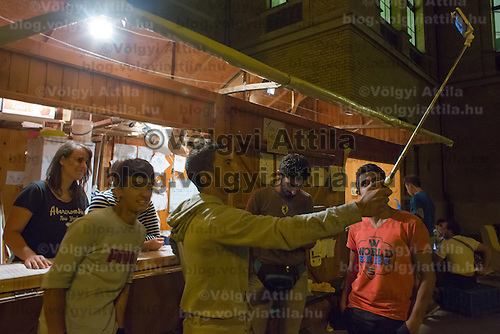 Illegal migrants take a selfie with volunteers at the transit zone at the railway station in Szeged (about 173 km South of capital city Budapest), Hungary on September 01, 2015. ATTILA VOLGYI