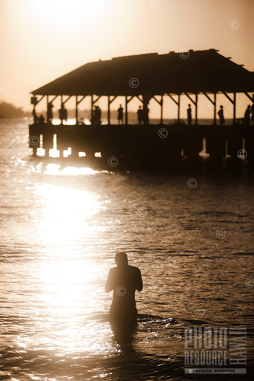 A silhouetted figure at Kauai's Hanalei Pier during a golden sunset