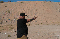 A militia member who serves as Cliven Bundy's personal bodyguard practices with his sidearm at camp &quot;Liberty&quot; near the Cliven Bundy ranch in Bunkerville, Nevada.<br />