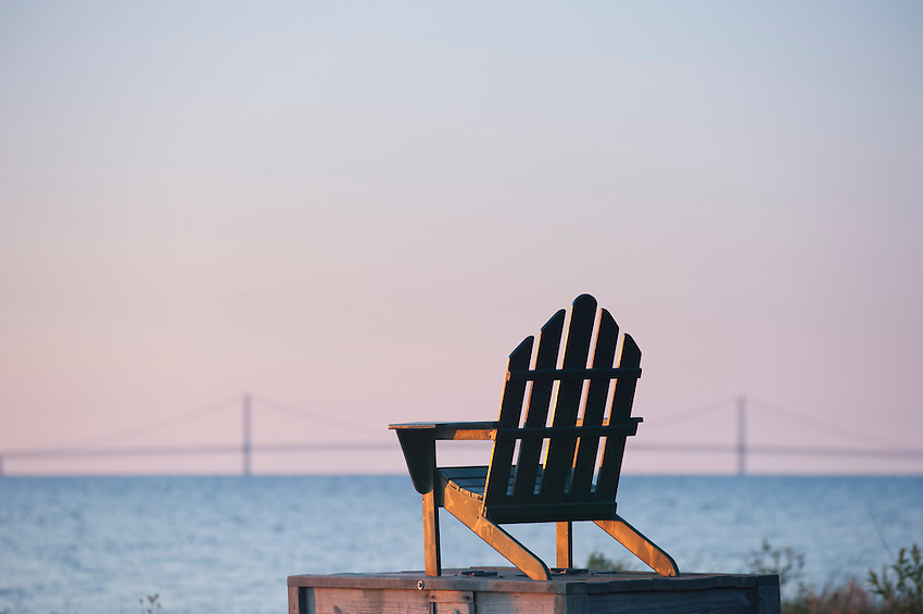 The Mackinac Bridge is seen behind a chair on the dock at St. Helena Island Lighthouse on Lake Michigan near Mackinaw City, Michigan.