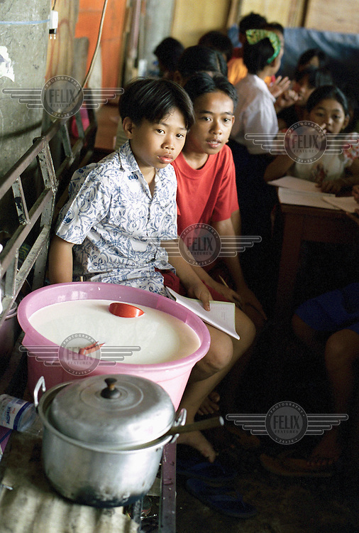 Children sit next to a bucket of milk, which is shared out between the students every day by school organisers, at an improvised Kartini school for slum-dwelling children.  It is constructed amongst piles of collected paper and cardboard under the toll road in Rawat Gedong Panjang region to the North of the city.  Raden Adjeng (Ayu) Kartini was a national heroine at the turn of the 20th century, who inspired women of her generation to strive for education, fight injustice and to achieve more than what society would allow them.
