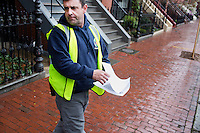 John Mullaney, temporary supervisor for construction for the Boston Public Works Department, looks at a printout showing a member of the public's complaint about specific road or sidewalk conditions in Boston, Massachusetts, USA, on April 12, 2012.  The city uses a computer system to track public complaints and record work done by city crews to mitigate these complaints.  A supervisor or inspector photographs before and after pictures of the work in addition to making notes about the work done.