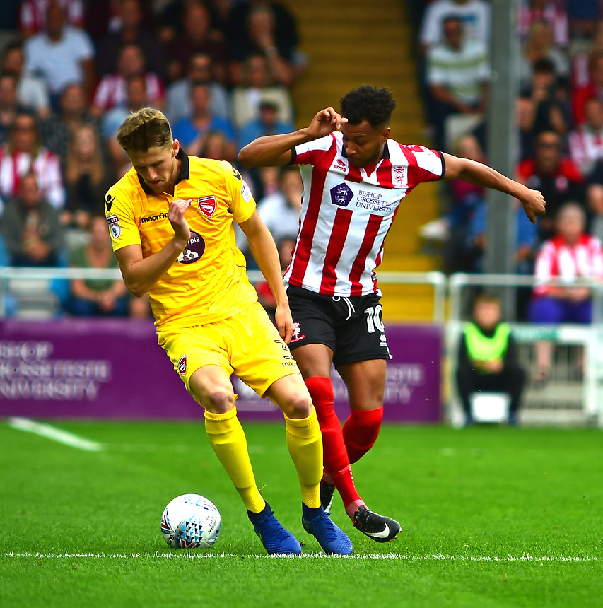 Lincoln City's Matt Green vies for possession with Morecambe's Patrick Brough<br /> <br /> Photographer Andrew Vaughan/CameraSport<br /> <br /> The EFL Sky Bet League Two - Lincoln City v Morecambe - Saturday August 12th 2017 - Sincil Bank - Lincoln<br /> <br /> World Copyright &copy; 2017 CameraSport. All rights reserved. 43 Linden Ave. Countesthorpe. Leicester. England. LE8 5PG - Tel: +44 (0) 116 277 4147 - admin@camerasport.com - www.camerasport.com