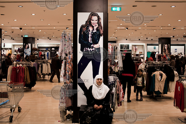 A woman takes a rest in a busy clothes shop in the Family Mall in downtown Erbil. Family Mall, built and owned by Turkish investors, is one of several new super malls built in recent years.