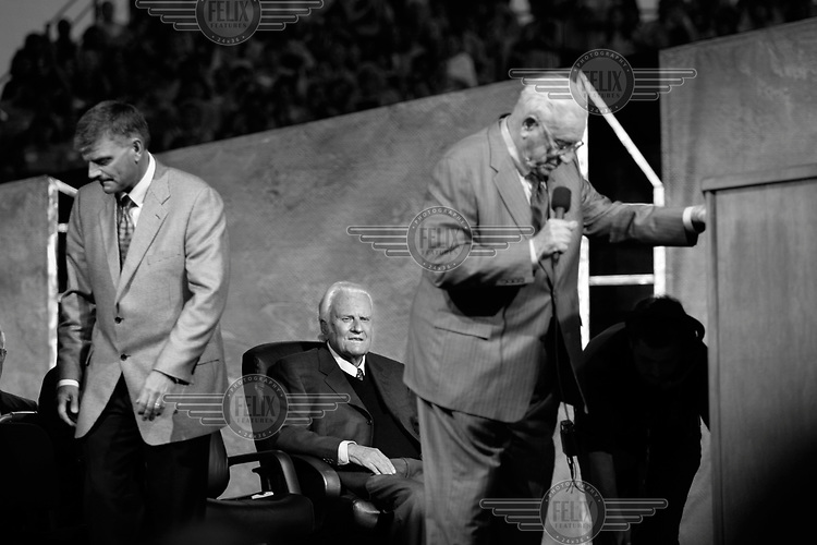 Christian evangelist Billy Graham sits on the stage at his crusade held at Flushing Meadows in New York City.