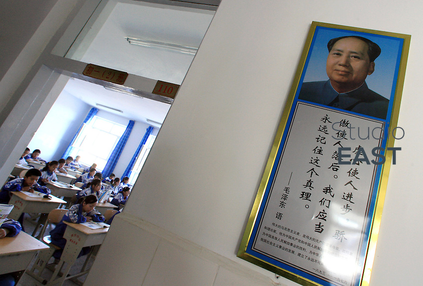 Uyghur students study Mandarin Chinese by a portrait of Mao Zedong in Hetian Experimental Billingual School, in Hetian, Xinjiang province, China, on October 13, 2006. The Uyghur people are a Turkic ethnic group living mainly in the Xinjiang Uyghur Autonomous Region of China. Photo by Lucas Schifres/Pictobank
