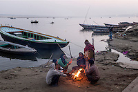 Indian men warms them with a fire at a ghat in Varanasi, Uttar Pradesh, India.