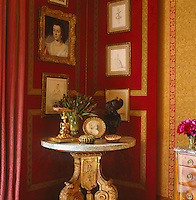 The master bedroom has a damask-covered corner screen on which is displayed a collection of framed artwork