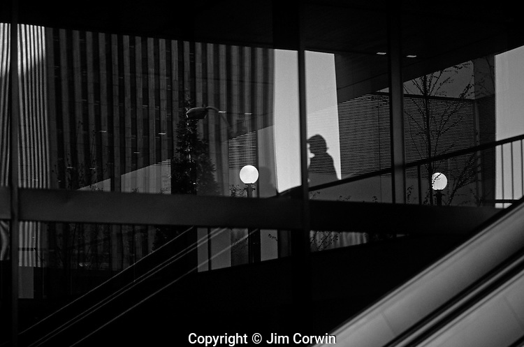 Silhouetted woman in a complex pattern of reflections from windows in an office building