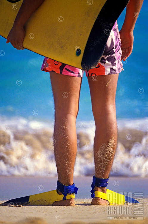 Bottom half of a young boy facing the surf wearing swim trunks and yellow fins with a yellow body board under his left arm.