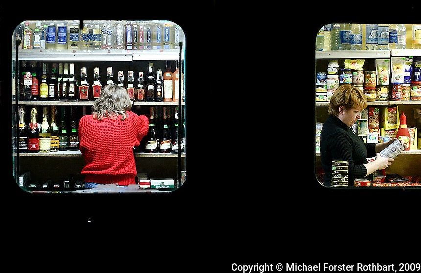 In Sukachi, Ukraine, a small food and liquor store in a converted trailer doubles as the village bar. Nina Dubrovskaya was a librarian, but she only earned $100 per month. It wasn't enough. Now she works up to twelve hours per day here and earns about $200 per month.  <br /> ------------------- <br /> This photograph is part of Michael Forster Rothbart's After Chernobyl documentary photography project.<br /> &copy; Michael Forster Rothbart 2007-2010.<br /> www.afterchernobyl.com<br /> www.mfrphoto.com <br /> 607-267-4893 o 607-432-5984<br /> 5 Draper St, Oneonta, NY 13820<br /> 86 Three Mile Pond Rd, Vassalboro, ME 04989<br /> info@mfrphoto.com<br /> Photo by: Michael Forster Rothbart<br /> Date:  11/2008    File#:  Canon 20D digital camera frame 11371 <br /> ------------------- <br /> Original caption: .In Sukachi, Ukraine, a small food and liquor store in a converted trailer doubles as the village bar. The store's two employees restock shelves and drink tea in the evening. They work up to twelve hours per day and earn about US$200 per month. Sukachi, a village of about 2,000, is south of the Chernobyl Exclusion Zone..-------------------.