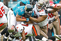 December 11, 2011:  Jacksonville Jaguars running back Maurice Jones-Drew (32) is tackled by Tampa Bay Buccaneers defensive tackle Brian Price (92) during first half action between the Jacksonville Jaguars and the Tampa Bay Buccaneers played at EverBank Field in Jacksonville, Florida.  ........