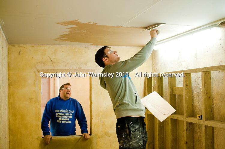 Plastering student usin g a trowel to apply fresh plaster overhead, Able Skills, Dartford, Kent.