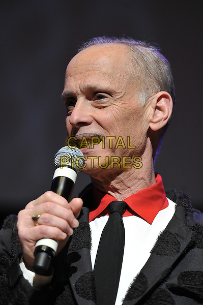 John Waters performing his one man show, 'A John Waters Christmas', Royal Festival Hall, London, England. .5th December 2011.stage concert live gig performance black polka dot jacket microphone headshot portrait red collar moustache mustache facial hair .CAP/MAR.© Martin Harris/Capital Pictures.