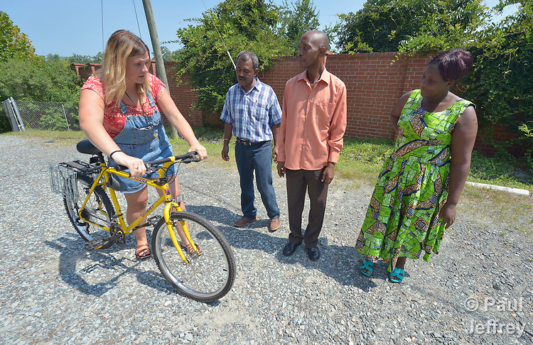 Monique Lohmeyer, a case manager for Church World Service, demonstrates bicycle basics for three refugees in Durham, North Carolina. <br /> <br /> Church World Service, which resettles refugees in North Carolina and throughout the United States, works with the Durham Bicycle Co-op to provide bikes to newly arrived refugees.<br /> <br /> <br /> <br /> Photo by Paul Jeffrey for Church World Service.