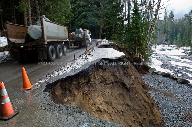 3/28/2007--Mt. Rainier National Park, WA, USA..Trucks from the Columbia Granite Quarry company haul giant rocks that will be dropped off the Nisqually Road (Highway 706) in Mt. Rainier National Park just south of Seattle. The rocks are intended to help rebuild parts of the road washed away by the Nisqually river during a storm in November, 2006. Many parts of the national park will stay closed, even through the summer season, due to extensive damage from the storm. The goal is to replace the earth beneath the road that the river washed away after a record 18 inches of rain fell in two days. ..Officials say the damage to popular routes through the park is unprecedented and caused in part by global warming. With glaciers retreating, sediment in rivers has built up to unprecedented levels, cause rivers to spill over faster in rain storms. Some national parks have been feeling the effects of climate change for years, including Glacier National Park in Montana and parks in Alaska...Parks in the West have been leading efforts to deal with climate change. To do so, officials say, they have to balance access and preservation. At the University of Washington, a multidepartmental collaboration known as Climate Impacts Group (CIG) puts a regional face on the global problem. In one recent report, CIG research scientist Philip Mote, together with 18 other scientists, documented the likely effects of global warming in the Northwest. Using seven different computer models to simulate future climatic conditions, they predicted more flooding in some rivers, when precipitation falls in sudden bursts of rain....COOL CITY.Seattle takes on the Global Warming Challenge.Photographs and text ©2007 Stuart Isett...In the winter of 2004 and 2005, Seattle Mayor Greg Nickels was hearing alarming reports from the nearby Cascade Mountains, the stunning snow capped peaks that sit just east of the city in Washington State, in the US Pacific Northwest. Nickels?s advisers were coming to him weekly wit