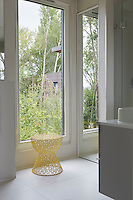 A delicate stool stands in front of the window in the bathroom. A mirrored wall reflects the light into the room.