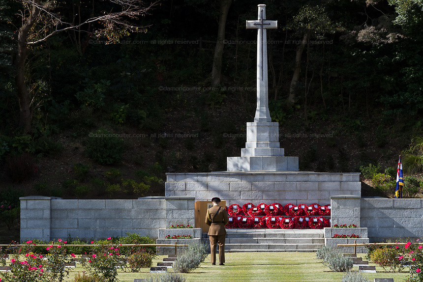 A Military office looks at the poppies that have been laid at the Cross of Sacrifice during the Remembrance Sunday ceremony at the Hodogaya, Commonwealth War Graves Cemetery in Hodogaya, Yokohama, Kanagawa, Japan. Sunday November 12th 2017. The Hodagaya Cemetery holds the remains of more than 1500 servicemen and women, from the Commonwealth but also from Holland and the United States, who died as prisoners of war or during the Allied occupation of Japan. Each year officials from the British and Commonwealth embassies, the British Legion and the British Chamber of Commerce honour the dead at a ceremony in this beautiful cemetery.