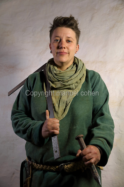 Aline Meunier, stone cutter on the Guedelon project since 01/08/2014, wearing medieval costume and holding a set square and chisel, at the Chateau de Guedelon, a castle built since 1997 using only medieval materials and processes, in Treigny, Yonne, Burgundy, France. The Guedelon project was begun in 1997 by Michel Guyot, owner of the nearby Chateau de Saint-Fargeau, with architect Jacques Moulin. It is an educational and scientific project with the aim of understanding medieval building techniques and the chateau should be completed in the 2020s. Picture by Manuel Cohen