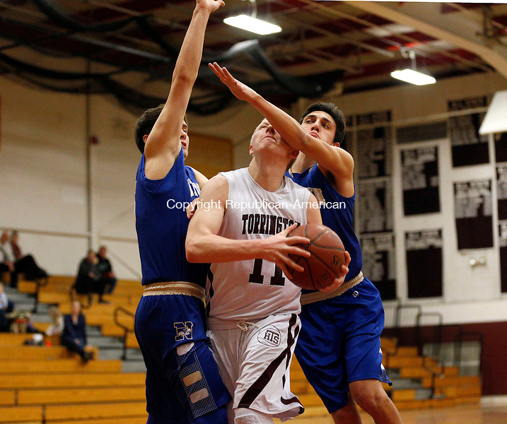 Torrington, CT- 11 January 2016-011116CM07-Torrington's Connor Finn is fouled as he moves to the basket against Newtown's Melillo Mason, left, and Sam Duffy during their non-conference matchup in Torrington on Monday.      Christopher Massa Republican-American