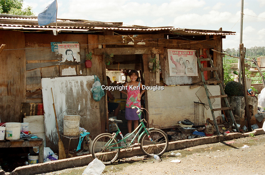 Young girl with bike in shanty town alongside Congressional Building, Asuncion, Paraguay.