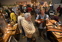 NWA Democrat-Gazette/ANDY SHUPE<br /> Bayard Blain (right), luthier and owner of Bayard Guitars in Fayetteville, shows a handmade ukulele to musician Todd J Maberry of Bentonville Thursday, Nov. 29, 2018, during the Little Craft Show inside the Fayetteville Town Center. First started in 2011, the holiday-themed show continues from 10 a.m. to 4 p.m. today.