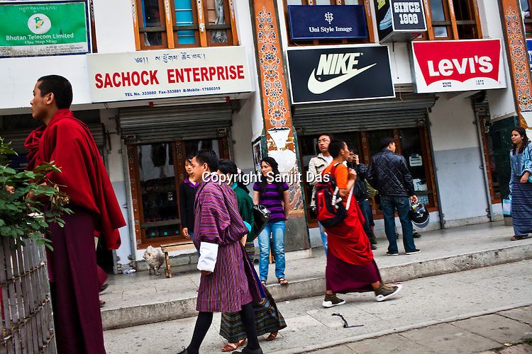 Buddhist Monks and Bhutanese dressed in both traditional and western outfits seen at the main market in Thimphu, Bhutan. Photo: Sanjit Das/Panos