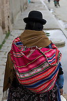 With around two-thirds of its population being indigenous Indians, Bolivia has the largest proportion of indigenous people in South America. Almost all the indigenous female population wear traditional dress, including a bowler hat perched on the top of their heads, a colourful woven shawl and a flouncy skirt. This woman was in Uyuni market.